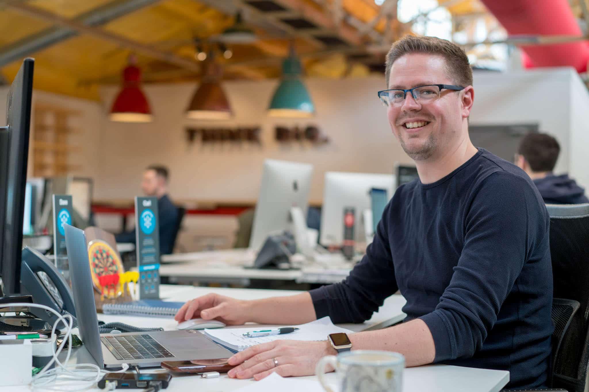 man working at desk smiling