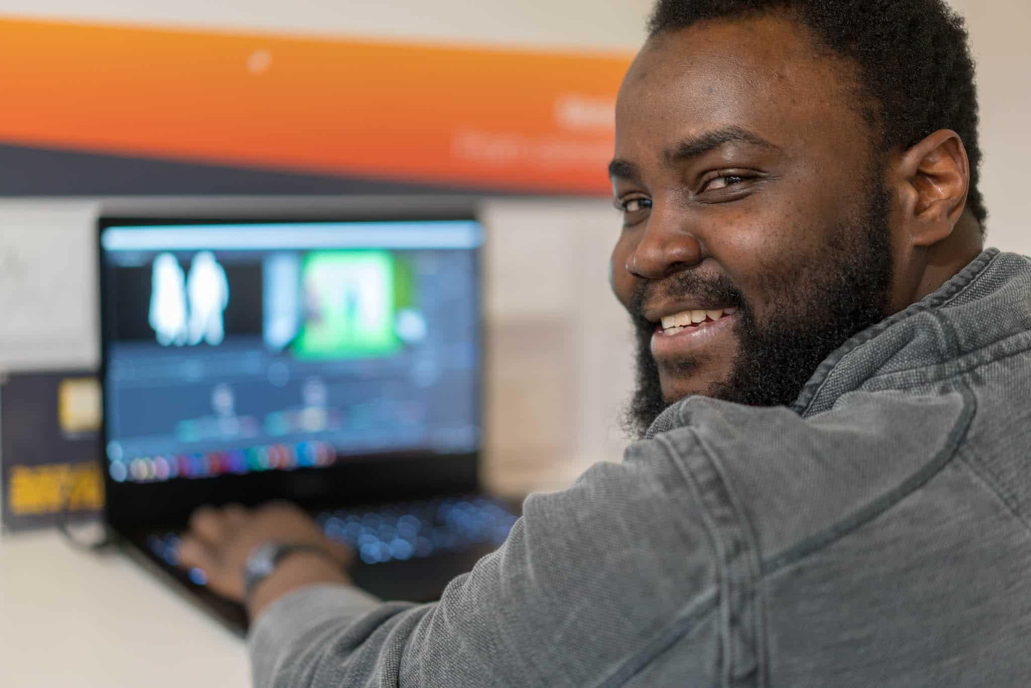 man smiling at camera whilst working on laptop