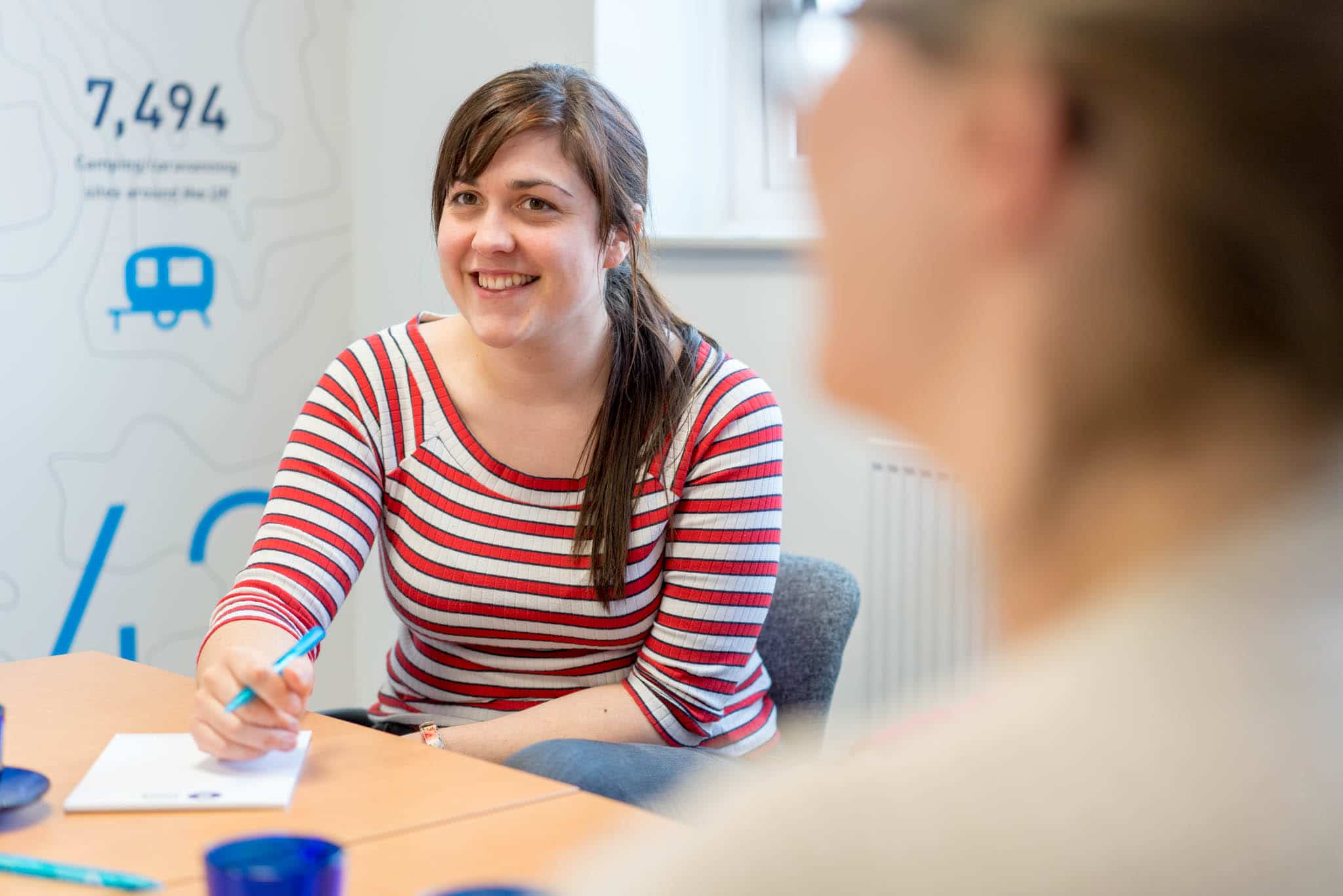 coronavirus financial support woman in stripy top smiling