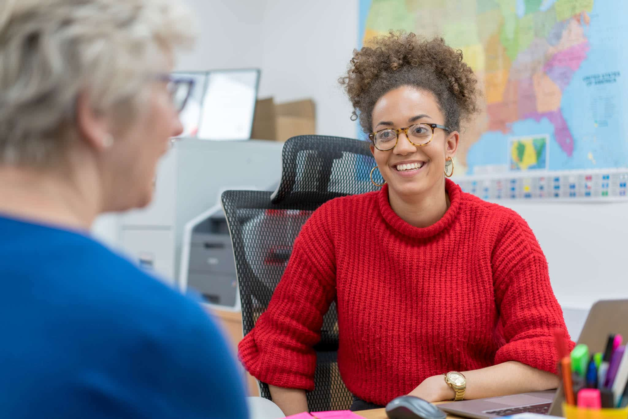 Charity Chamber of Commerce Membership, woman in red jumper sat at desk smiling