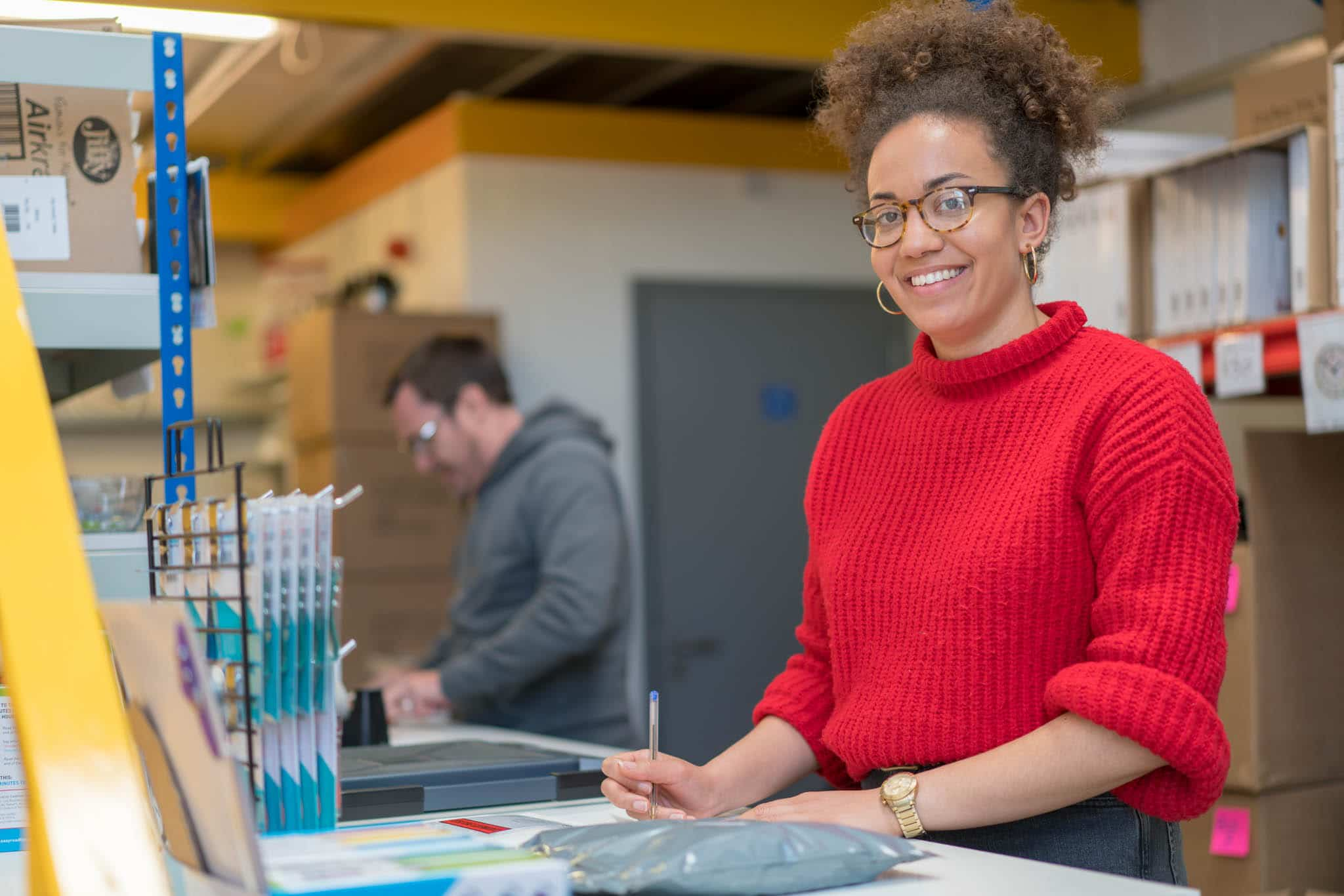 woman in red jumper smiling at camera writing legal status notes