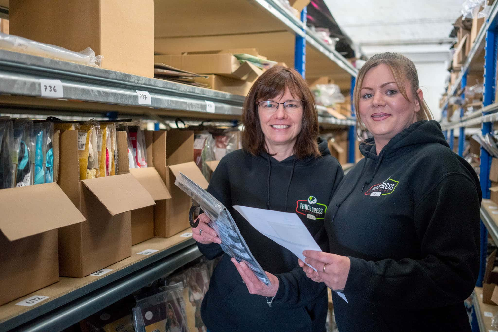 coronavirus financial support two women in a warehouse smiling at the camera
