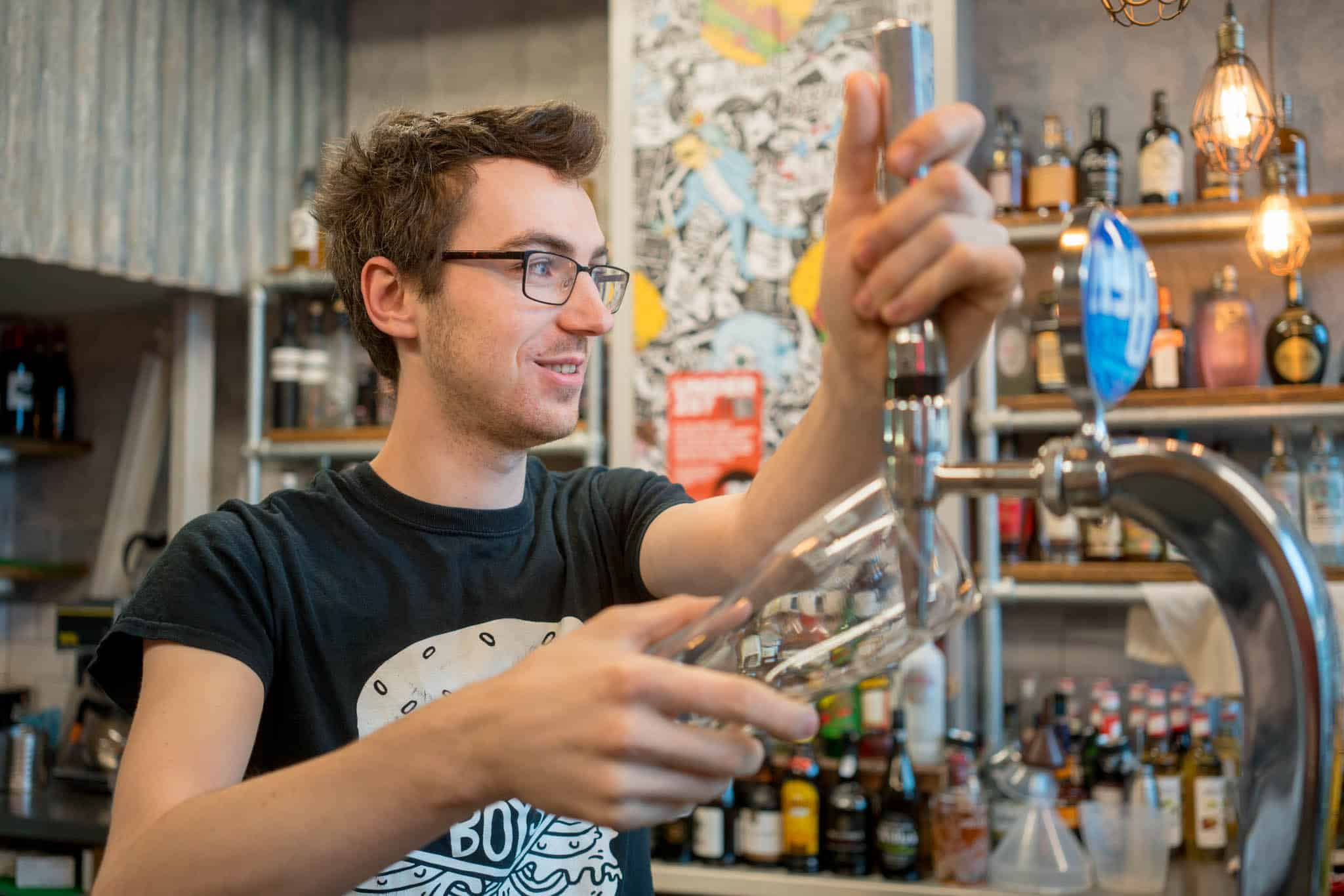 Man pouring beer into a glass with Patron Chamber of Commerce membership