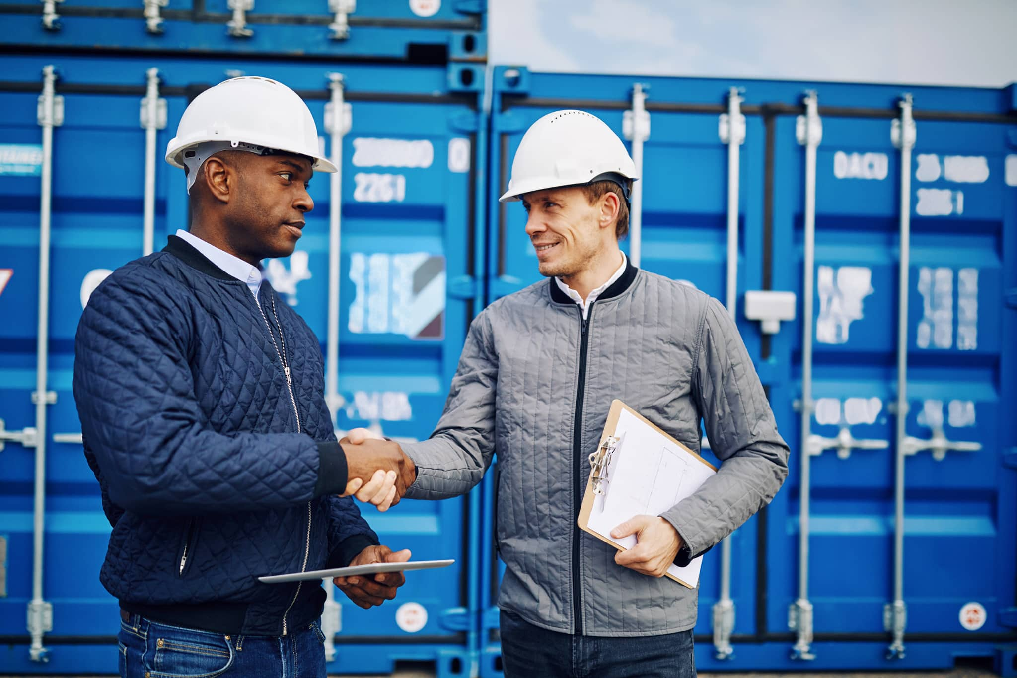 two men in building yard with hard hats, shaking hands