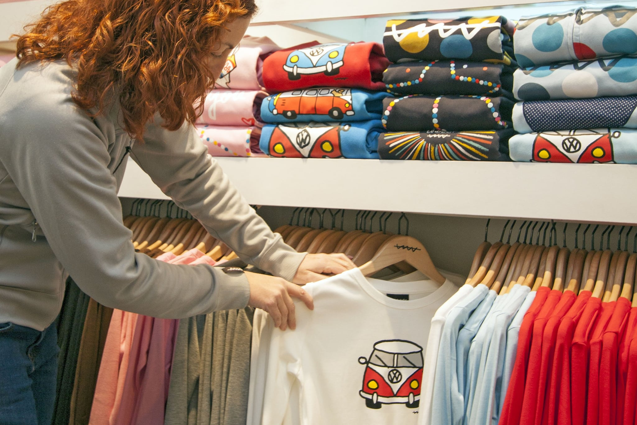woman with ginger hair looking at a jumper with a red camper van on